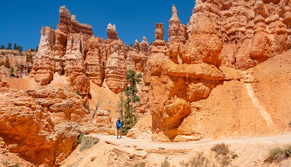 Man on hiking trip in mountains taking photos with his camera at Bryce Canyon