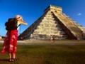 Mujer fotografiando la pirámide de Kukulcan en Chichén Itzá, Mexico, Visitando el Mundo Maya