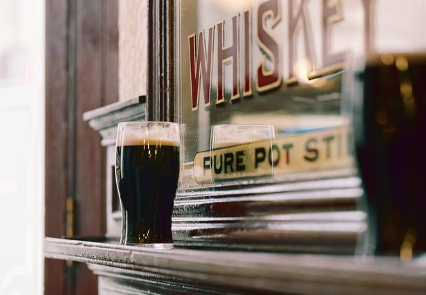 Dark beers sit on pub counter, Dublin, Ireland, Frommers: 10 Must-Do Overseas Trips