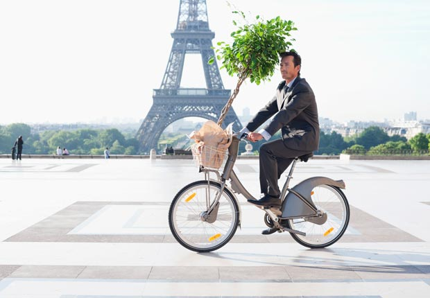 Man on bicycle in front of Eiffel Tower, Paris.