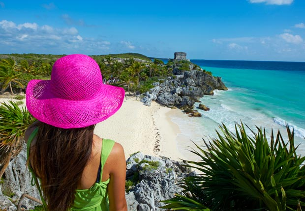 Woman in pink hat watching ocean, Tulum, Mexico