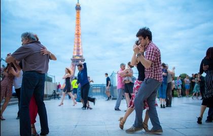 Pareja bailando con la Torre Eiffel de fondo - París entre luces