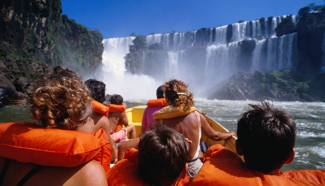 Tourists Sit In Boat With Life Jackets At Base Of Iguazu Falls In Argentina And Brazil, Best International Waterfalls