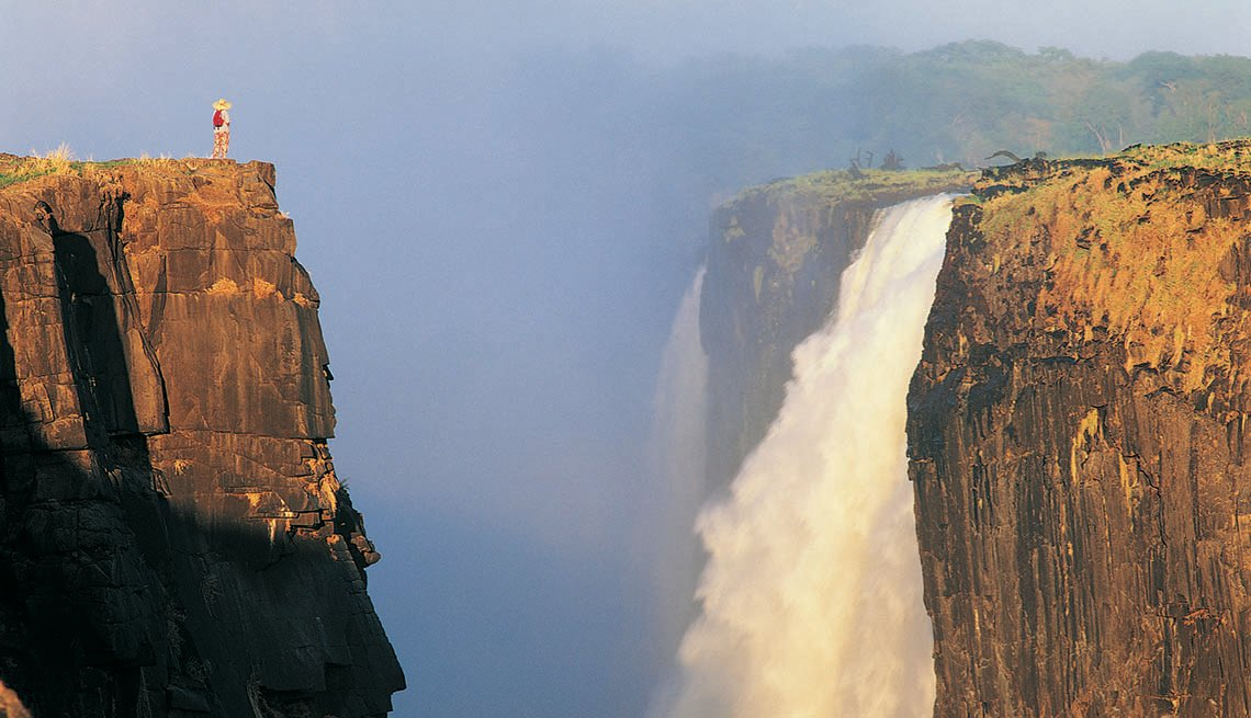 Woman Stands On Cliff Across From Victoria Falls In Zimbabwe, Best International Waterfalls