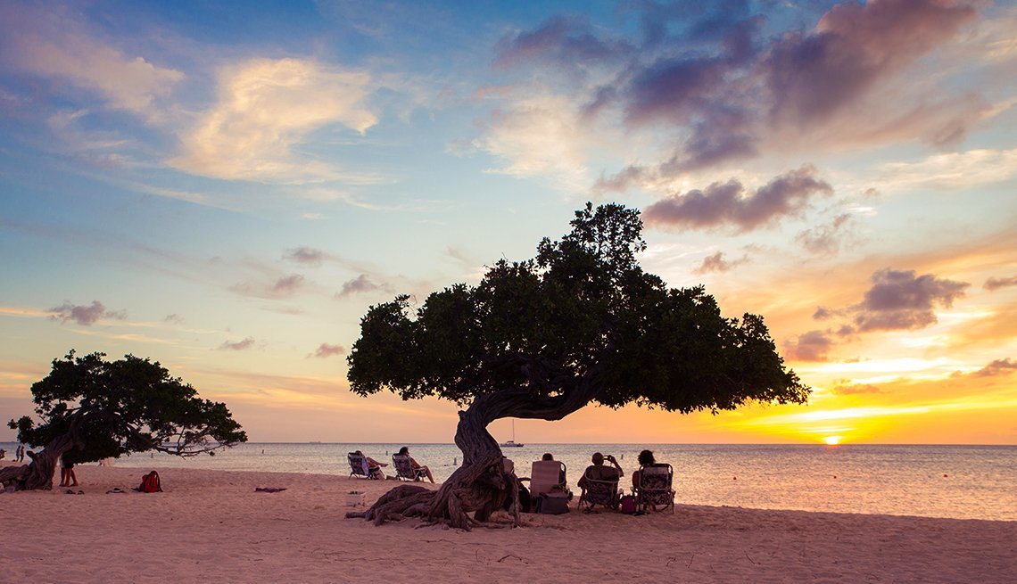 Tourists Watching Sunset Underneath Divi Divi Trees on Eagle Beach, Aruba, Caribbean Island Guide