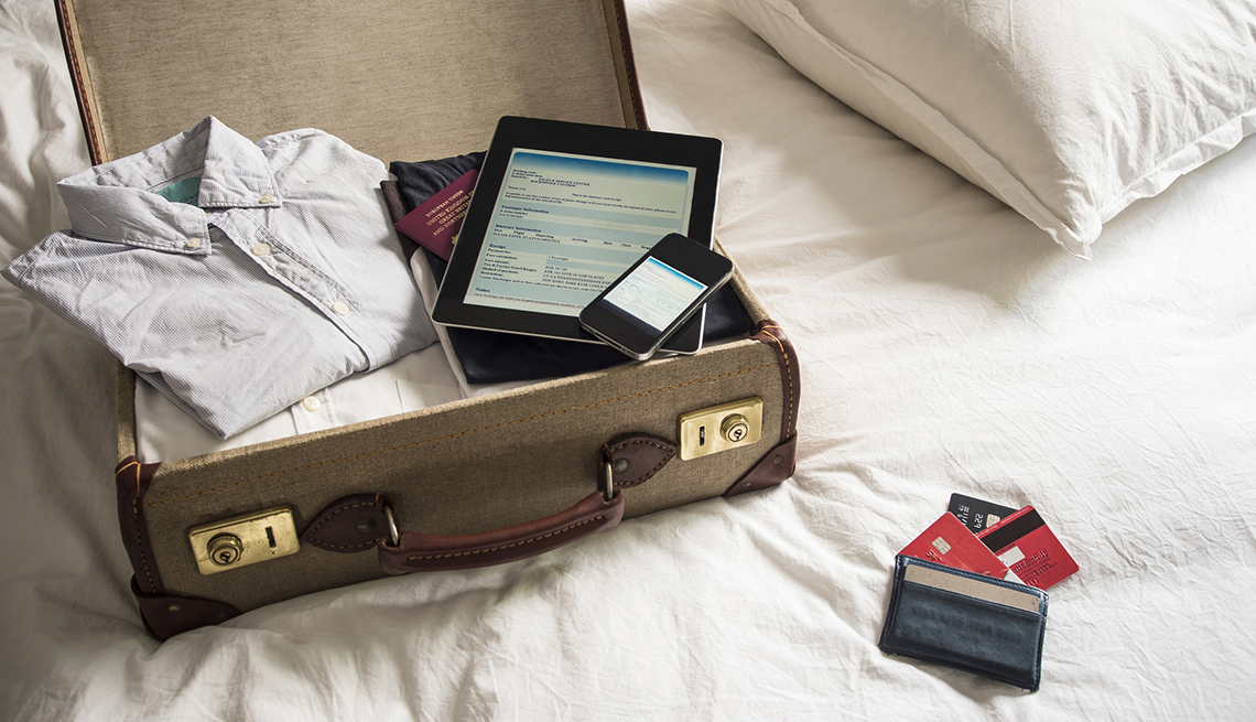 Suitcase on White Bed, Tablet. Smartphone. Credit Cards, Checklist for International Travel