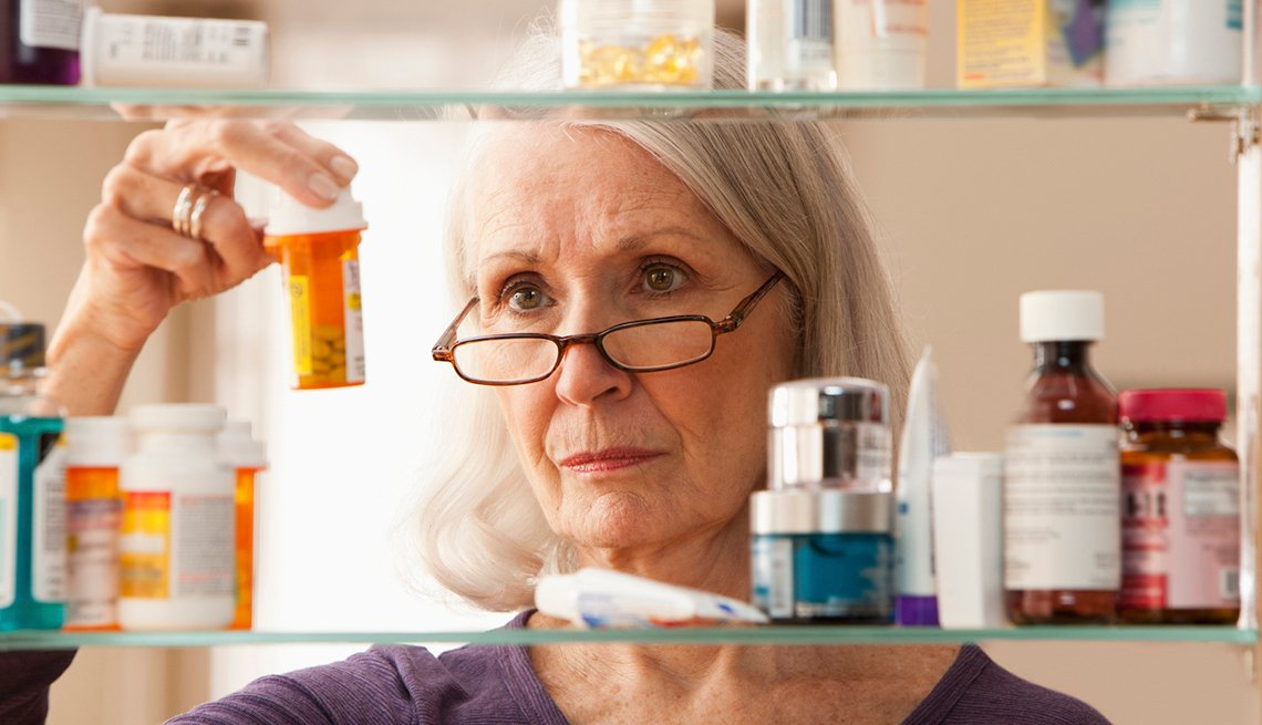 Senior Caucasian Woman, Medicine Cabinet, Pill Bottles, Checklist for International Travel
