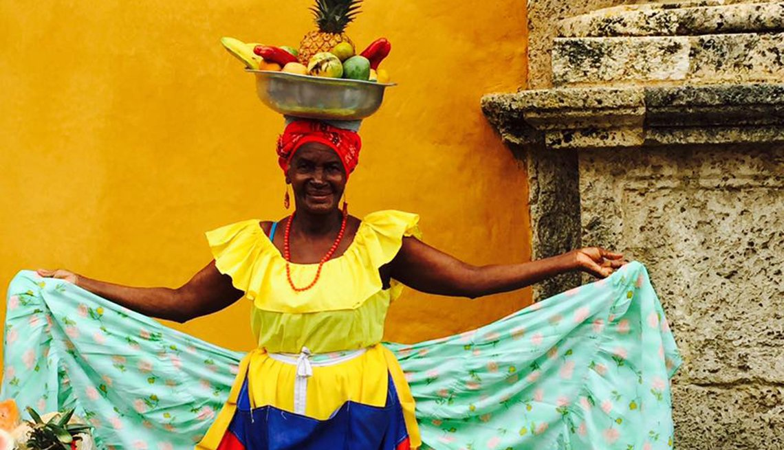 Woman In Colorful Dress Wears A Hat Topped With Fruit On Her Head, Colombia Slideshow