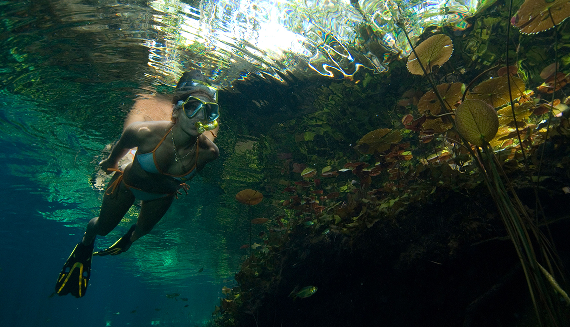 Woman Swims In Grand Cenote In Tulum, All Inclusive Mexican Resorts