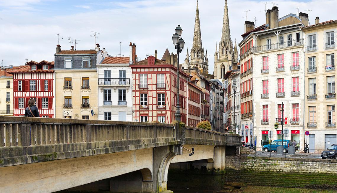 Un puente a edificios antiguos con torres gemelas de la Catedral detrás
