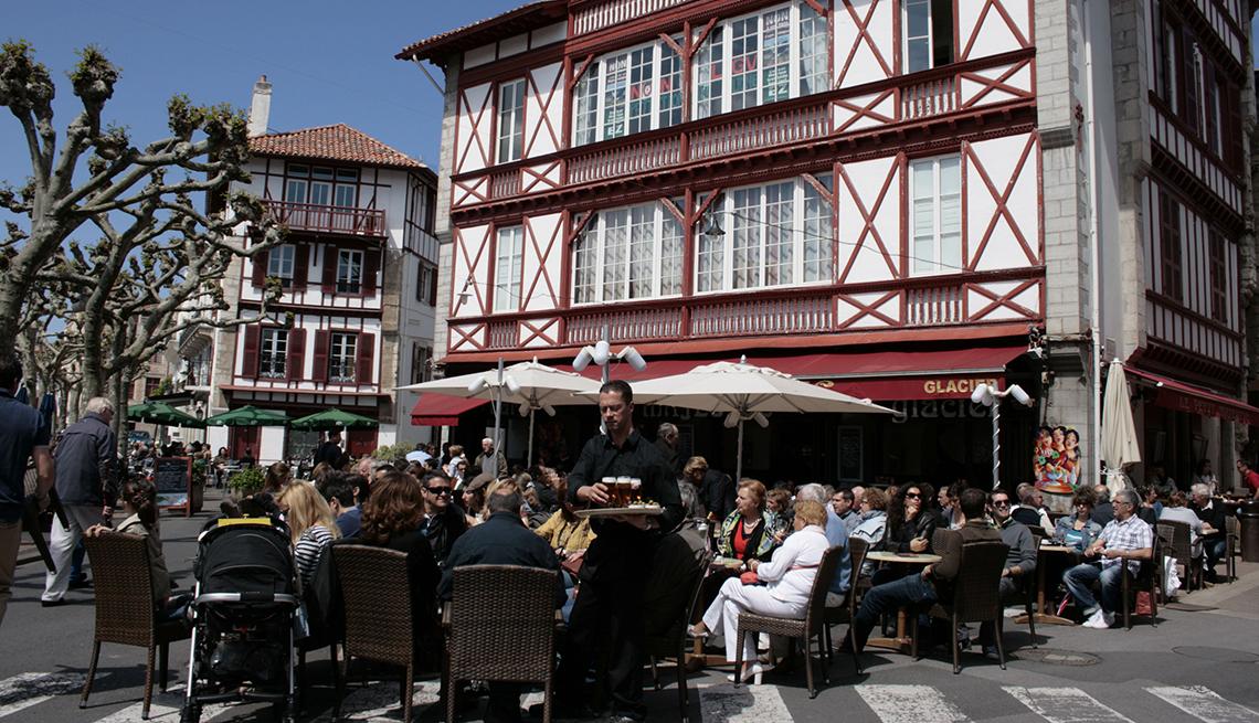 Un camarero ofrece vasos de cerveza en un café abarrotado en una plaza abierta.