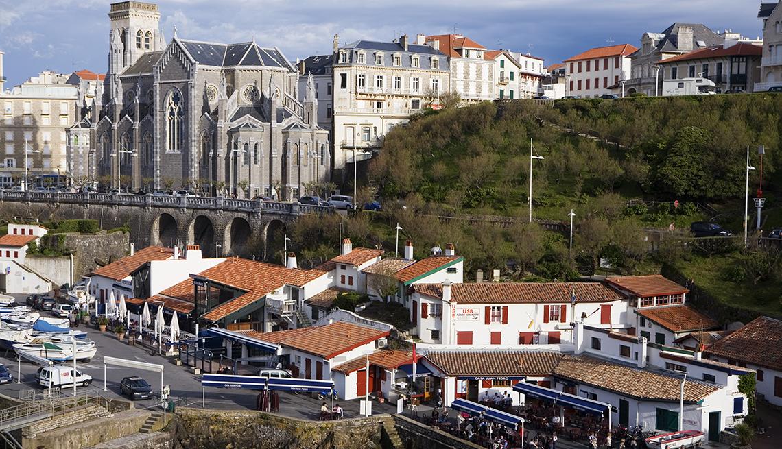 Edificios con tejas rojas en el puerto de Biarritz con la iglesia de San Eugenio en el horizonte.