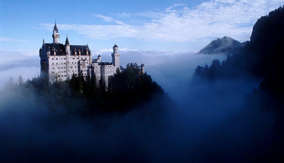 Castillo de varios torreones en la cima de la colina sobre el valle brumoso