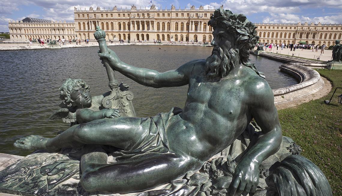 Estatua de bronce de Neptuno frente a una piscina frente al Palacio de Versalles