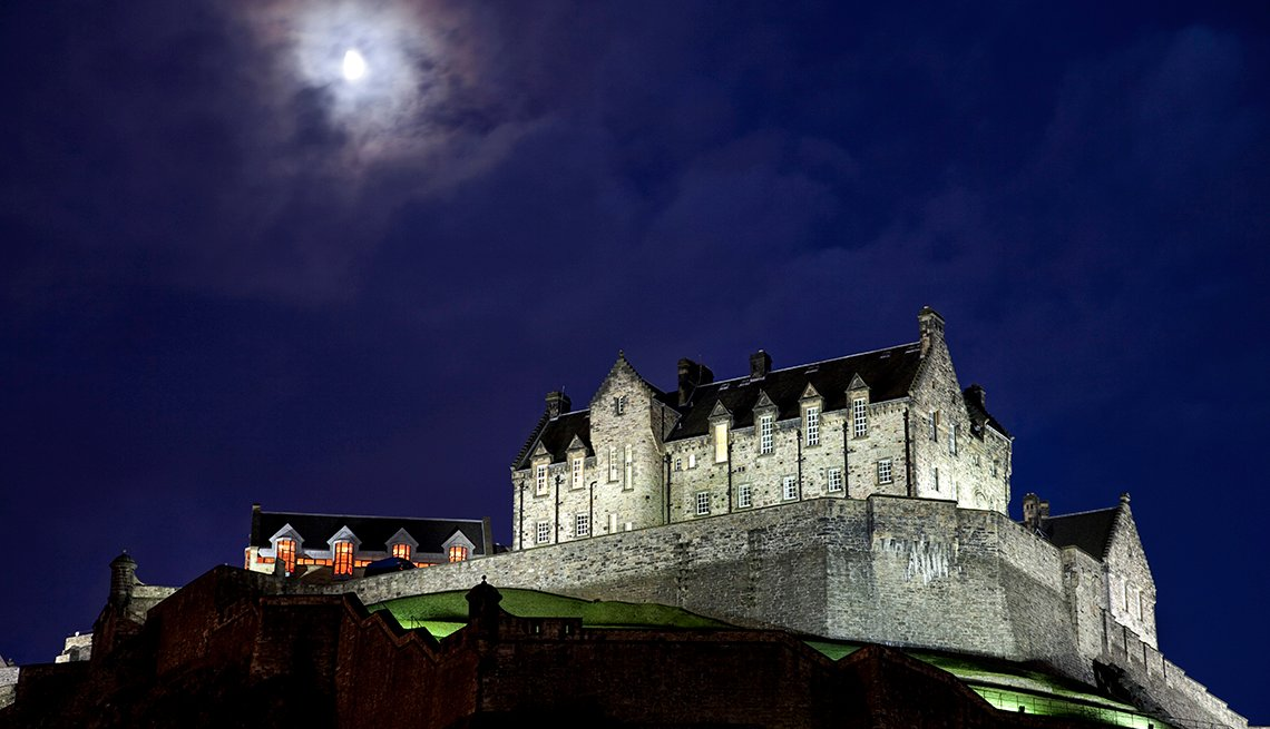 Luna en las nubes sobre Spotlit Castillo de Edimburgo en la noche
