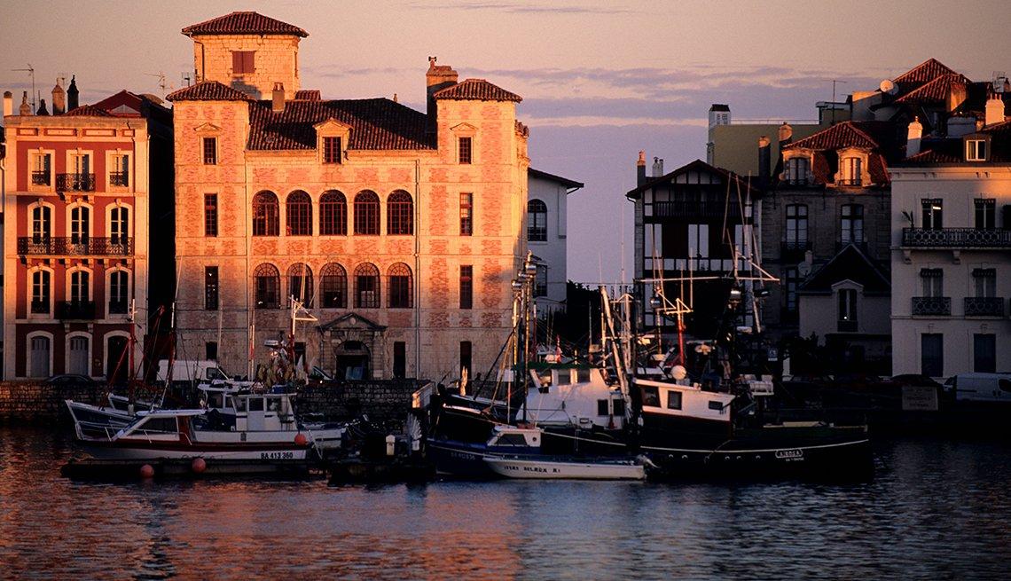 Luz del atardecer se posa sobre edificios en el puerto Saint Jean de Luz
