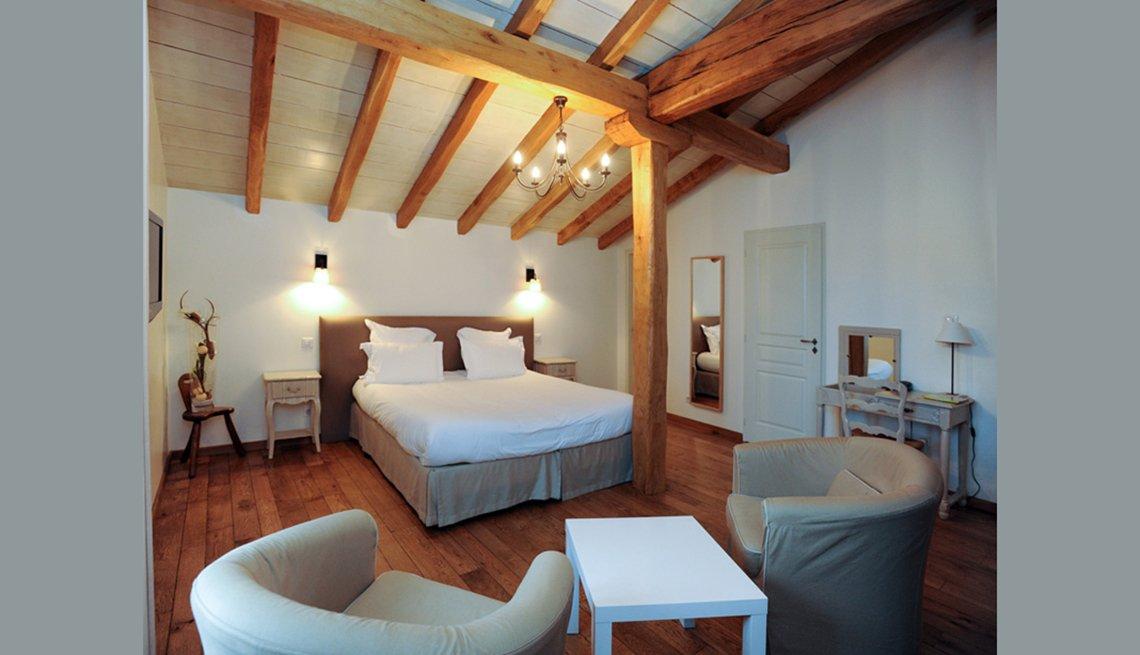 Cama y sala de estar en la habitación con vigas de madera y vigas