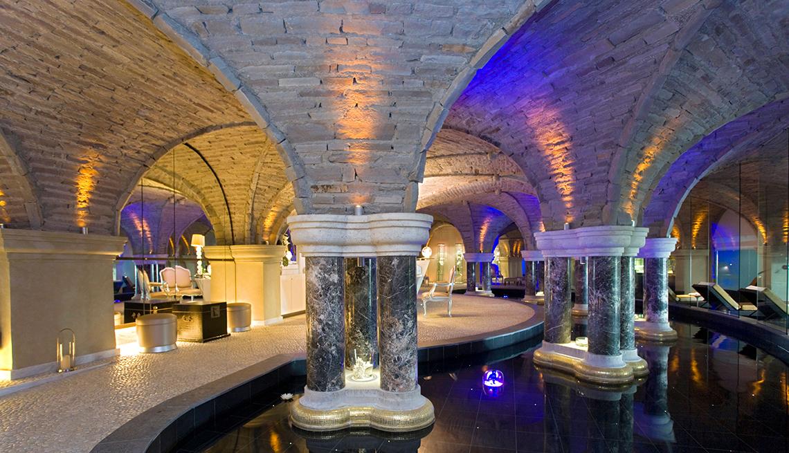 Arcos de piedra en un spa con focos de color púrpura y amarillo
