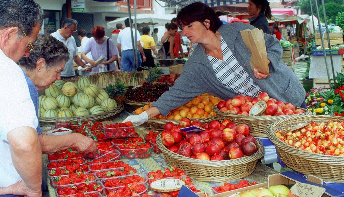 Los compradores seleccionan fresas frescas en un puesto de frutas en el mercado de Les Halles.