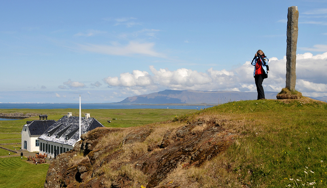 woman on a hill taking photos on Videy Island, Iceland