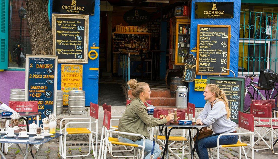 item 3, Gallery image. Restaurante colorido de La Boca, con mujeres jóvenes tomando una copa.
