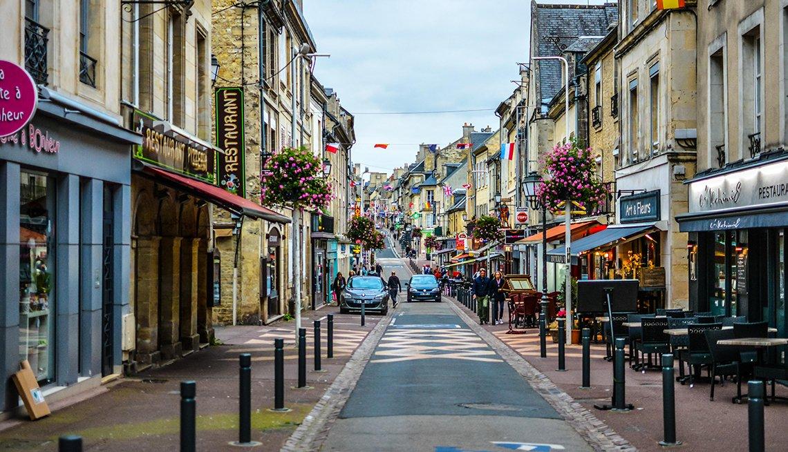 item 4, Gallery image. La larga calle, en un solo sentido, Rue Saint-Jean, llena de cafés y tiendas en la ciudad de Bayeux, Normandía.