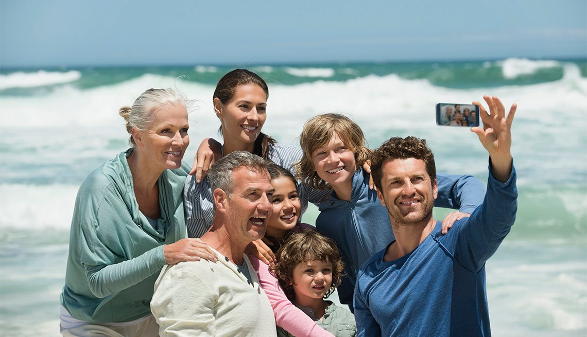 multi-generational family taking a selfie on a beach