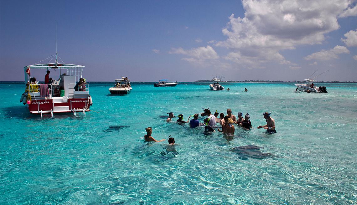 Gente tocando mantarrayas en el mar