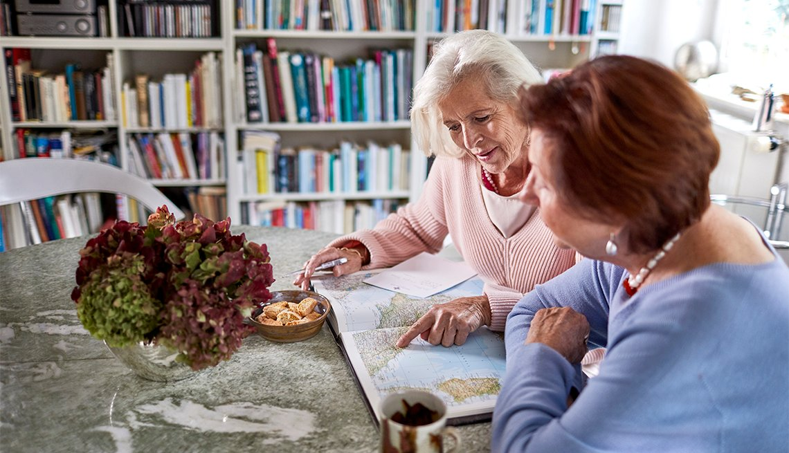 two women sitting at a table looking at a map, planning a trip