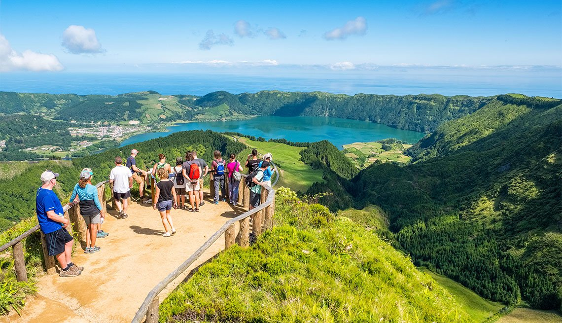 Tourists at a viewpoint over Sete Cidades, two lakes and a village in the dormant crater of a volcano on the island of Sao Miguel, The Azores