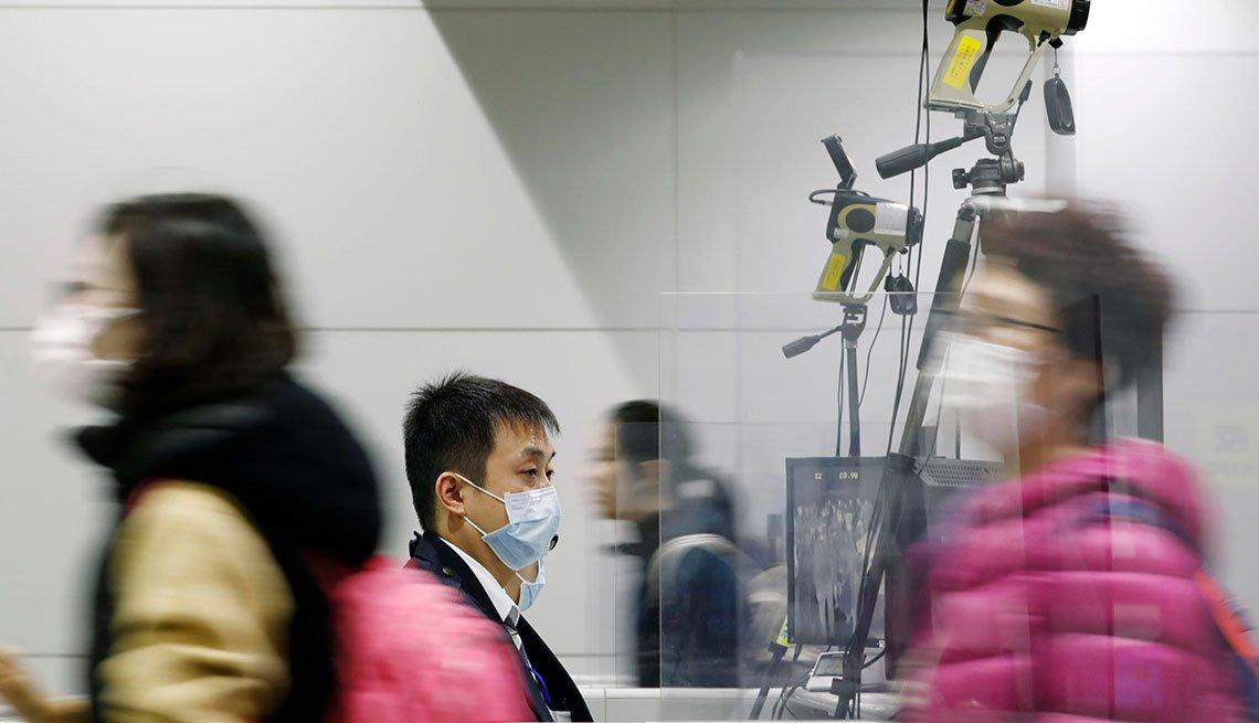 Personas transitan en un aeropuerto usando mascarillas para protegerse