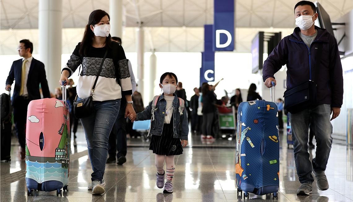 Viajeros con máscaras faciales caminan en el aeropuerto