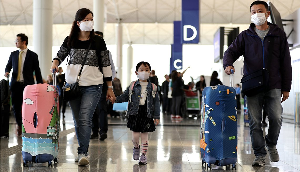Travelers wearing face masks and pushing suitcases walk through the check-in hall at the Hong Kong International Airport in Hong Kong, China, on Wednesday, Jan. 22, 2020. China ramped up efforts to contain a new respiratory virus thats killed nine people