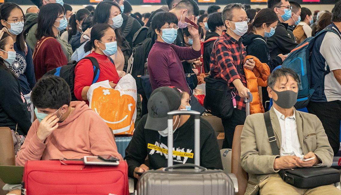 Viajeros con mascarillas en aeropuerto de Hong Kong, China.