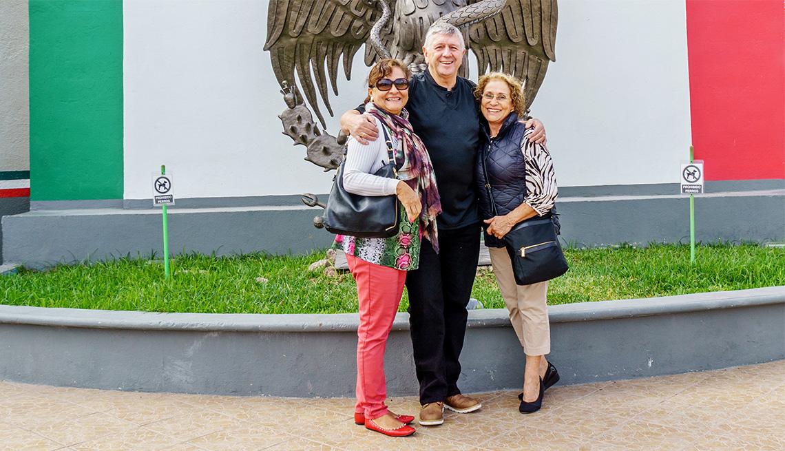 Three tourists on bridge between USA and Mexico