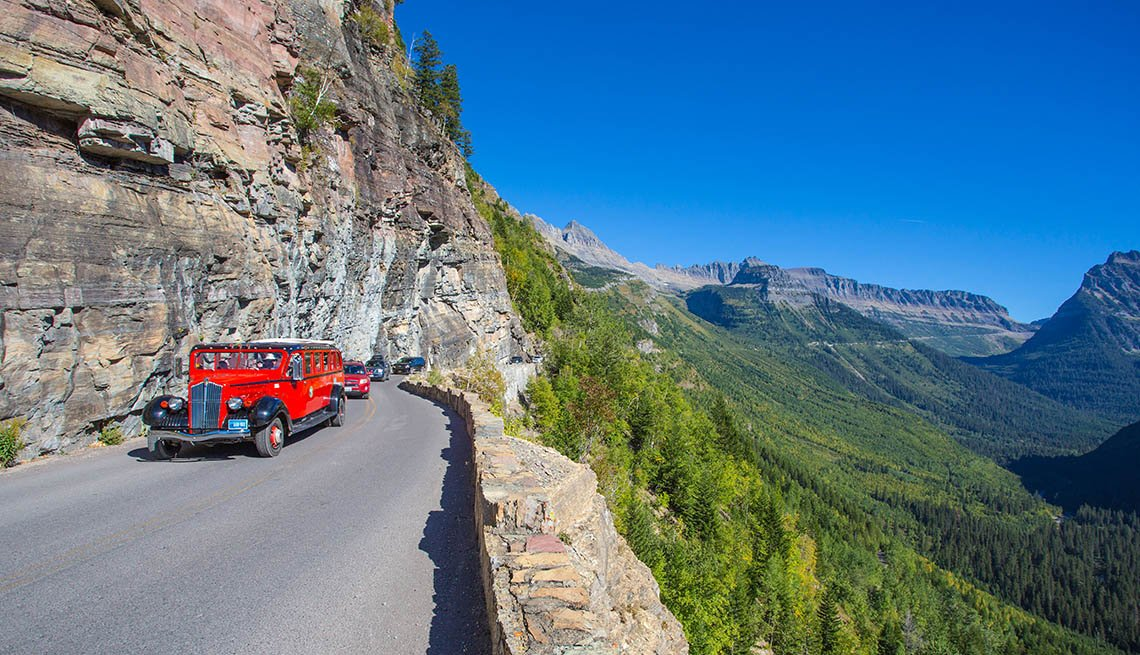 Red Vintage Car On A Road In The Glacier National Park In The Rocky Mountains Of Montana, 9 Great Summer Roadtrips