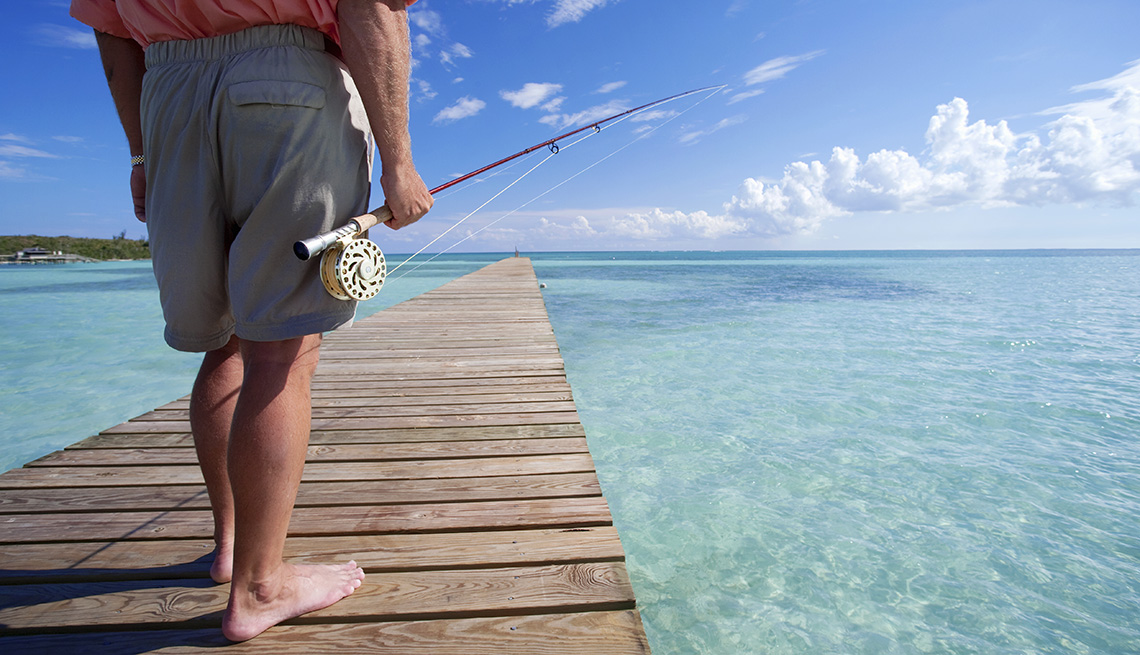 Man Stands On Dock With Fishing Rod In Bahamas, Sunny Holidays