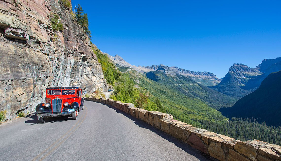 A Red Bus Makes Its Way Through The Mountain In Glacier National Park In Montana, National Parks Experiences