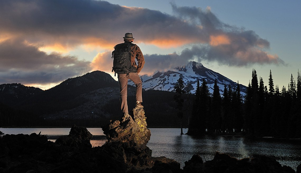 Male Hiker Looks At The Lake, Forest, Snowy Mountains At Sunrise In Sparks Lake Oregon, 5 Getaways For Guys