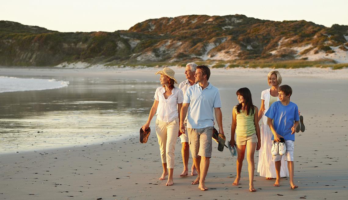 Familia caminando en la playa durante una tarde.