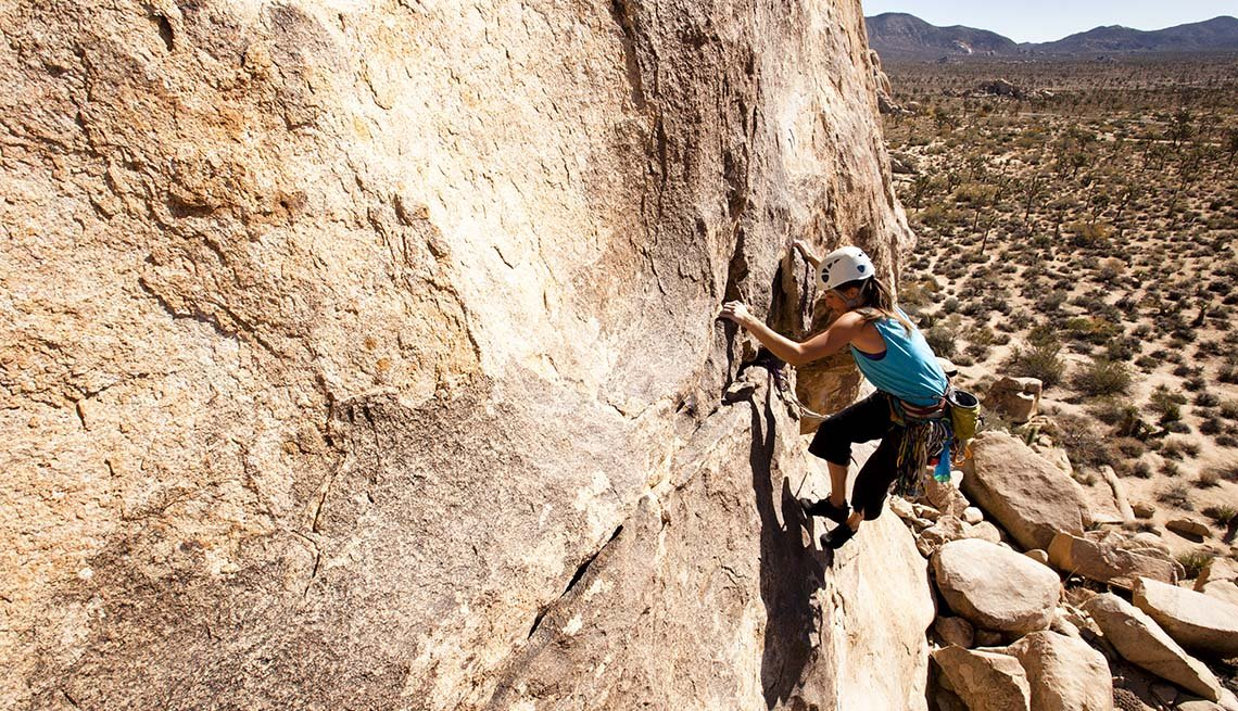 A Female Rock Climber In Joshua Tree National Park In California, National Parks Experiences