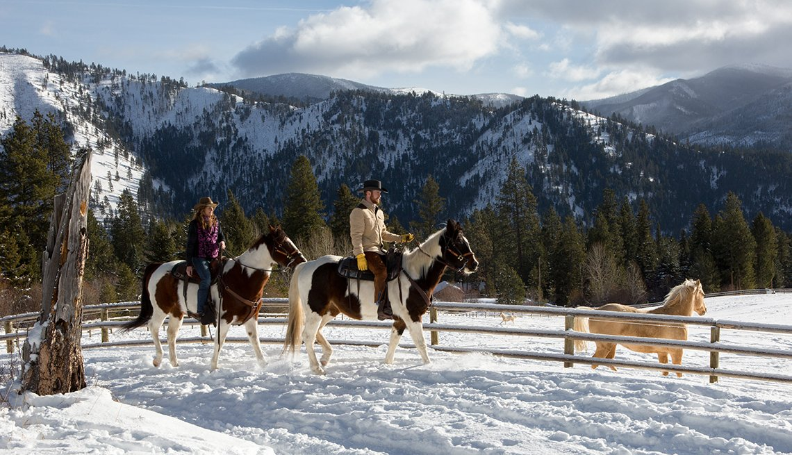 Caucasian Couple Ride Horses With Snow Capped Mountains In Background, Dude Ranch Vacations