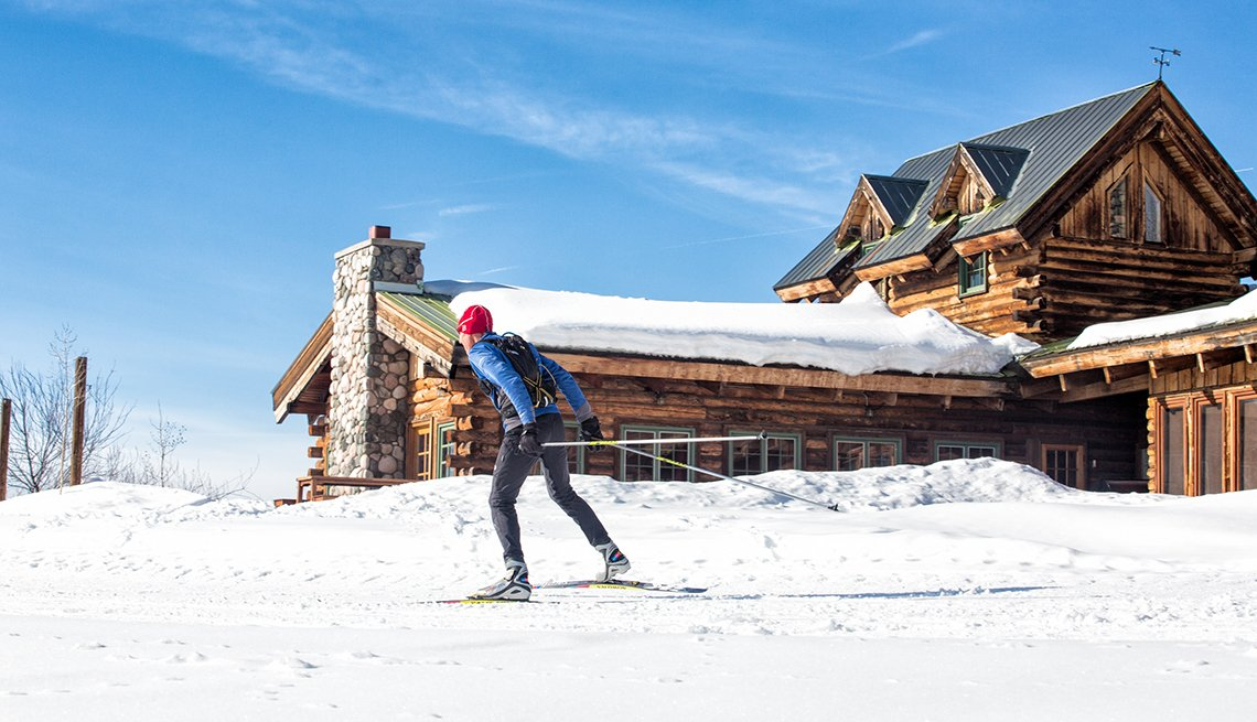 A Cross Country Skiier Passes A Log Cabin, Dude Ranch Vacations