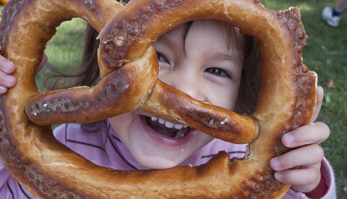 Little Caucasian Girl Holds Up A Giant Pretzel, Oktoberfest Destinations USA