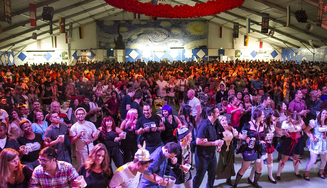 View Of The Great Hall Filled With People Holding Beer Glasses And Enjoy The Show, Oktoberfest Destinations USA