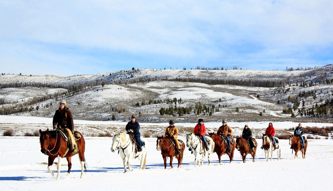 Group Of People On Horseback In Snow With Mountains In Background, Dude Ranch Vacations