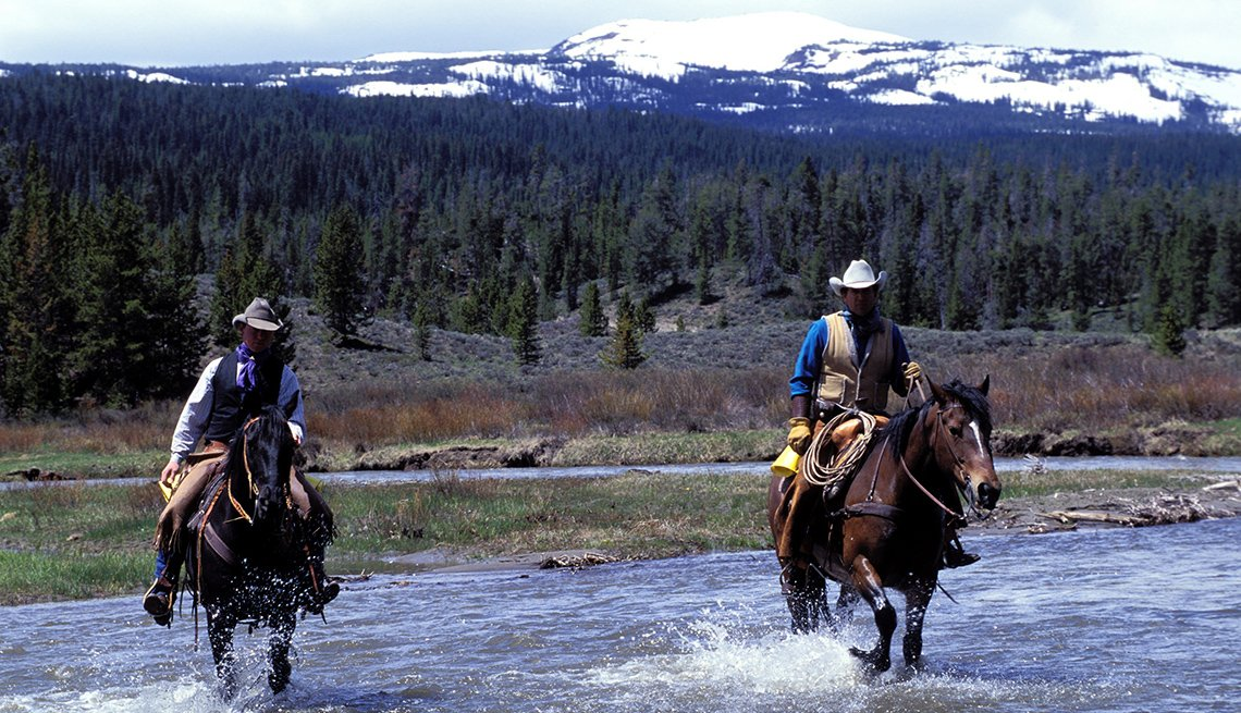 Two Cowboys On Horses Ride Through Low Creek With Mountains In Background, Dude Ranch Vacations