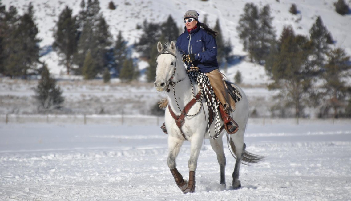Lone Woman Rides Her Horse Through Snow, Dude Ranch Vacations