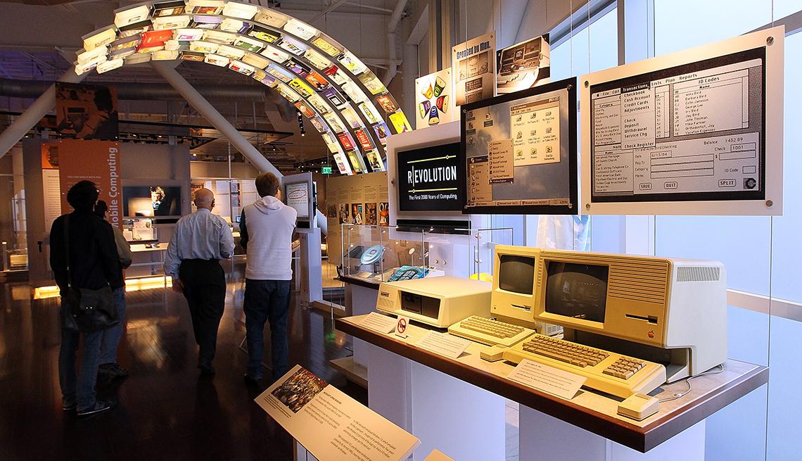 Computadoras Apple originales en exhibición mientras la gente mira la exhibición del museo