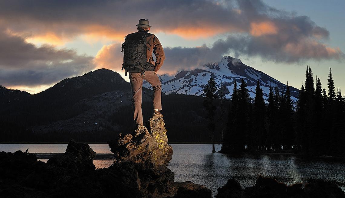 Hombre mirando una montaña en el horizonte